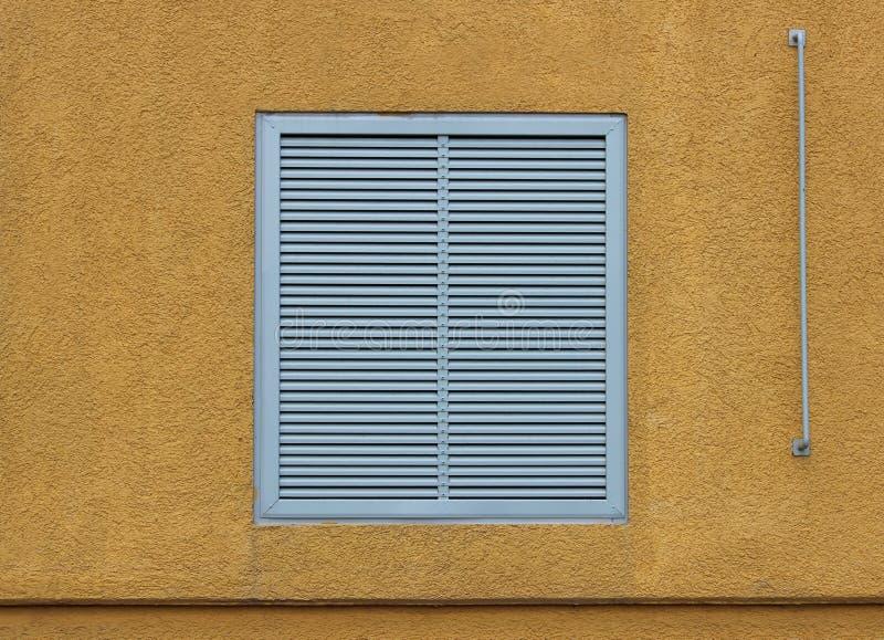 Een venster in een groot industrieel winkelcentrum sloot met externe jaloezie in de vorm van ventilatietraliewerk geeloranje bei stock foto's
