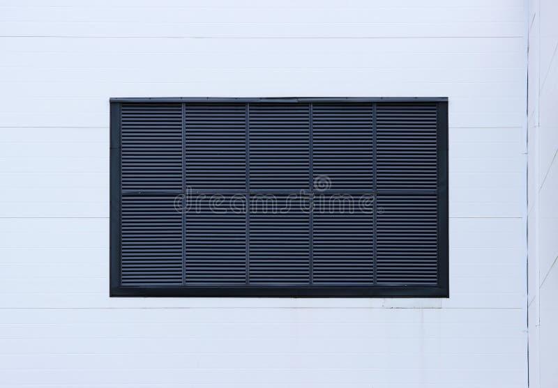 Een venster in een groot industrieel winkelcentrum sloot met externe jaloezie in de vorm van ventilatietraliewerk Lichtblauwe bac stock foto's
