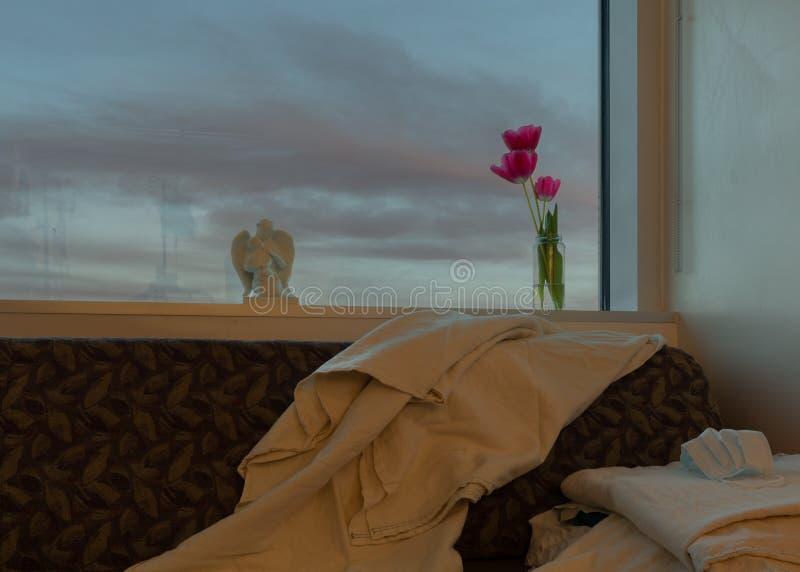 Een venster in een het ziekenhuisruimte met avond betrekt binnen buiten en bloemen in een kruik, een engelenstandbeeld sommige de stock afbeeldingen