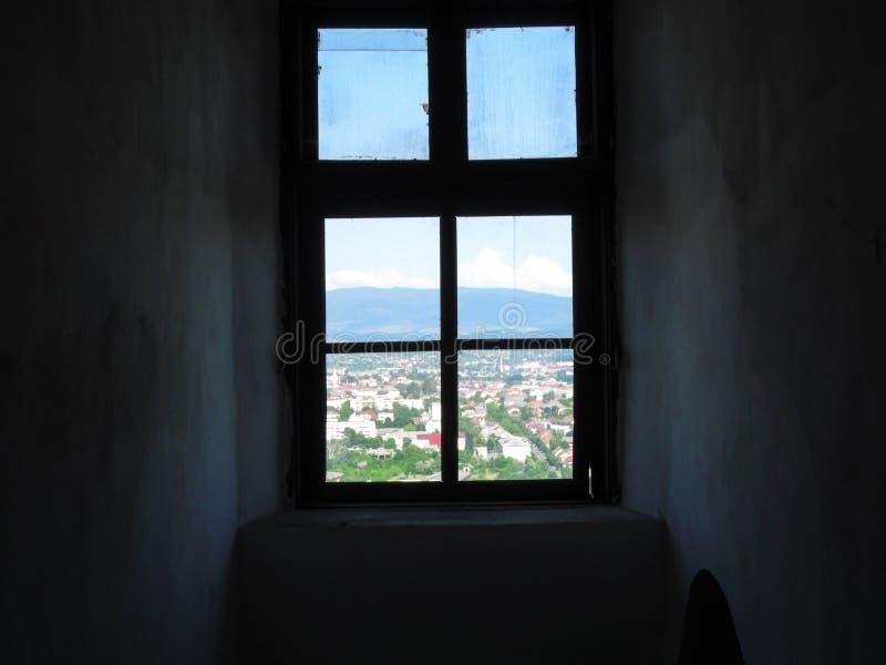 Een venster van een donkere sombere ruimte in een heldere zonnige wereld Oud sjofel venster met vuile glazen, de donkere muren en royalty-vrije stock foto