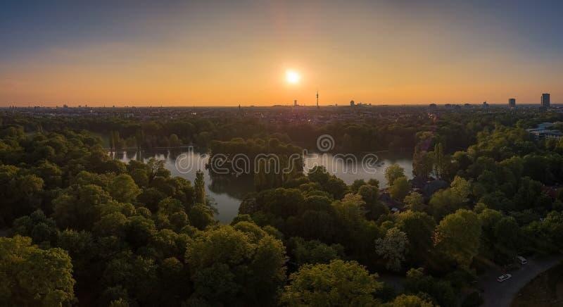 Een verbazende die zonsondergang over een meer, door bomen in München, Beieren wordt omringd stock foto