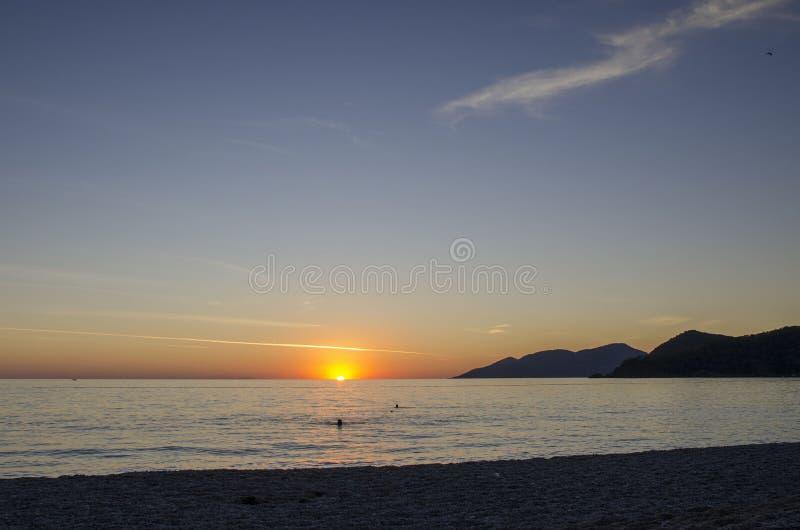 Een verbazende mening van de Turkse kust, op de horizon de zon daalt in het overzees, aan het recht is een mening van de bergen stock foto's