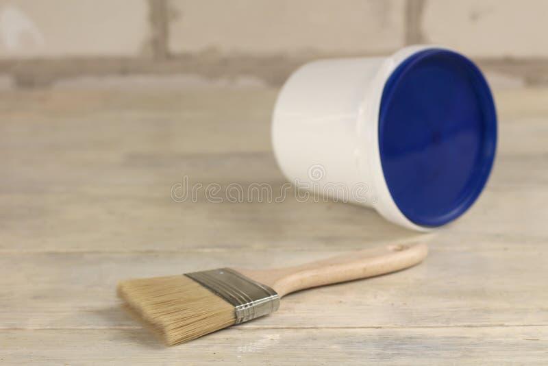 Een verfborstel is naast een plastic verfemmer met een blauw deksel op een oude witte uitstekende houten raad Bakstenen muur op d stock foto