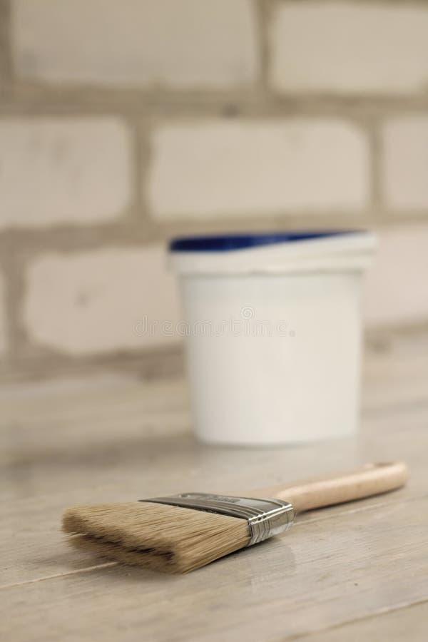 Een verfborstel is naast een plastic verfemmer met een blauw deksel op een oude witte uitstekende houten raad Bakstenen muur op d stock afbeeldingen