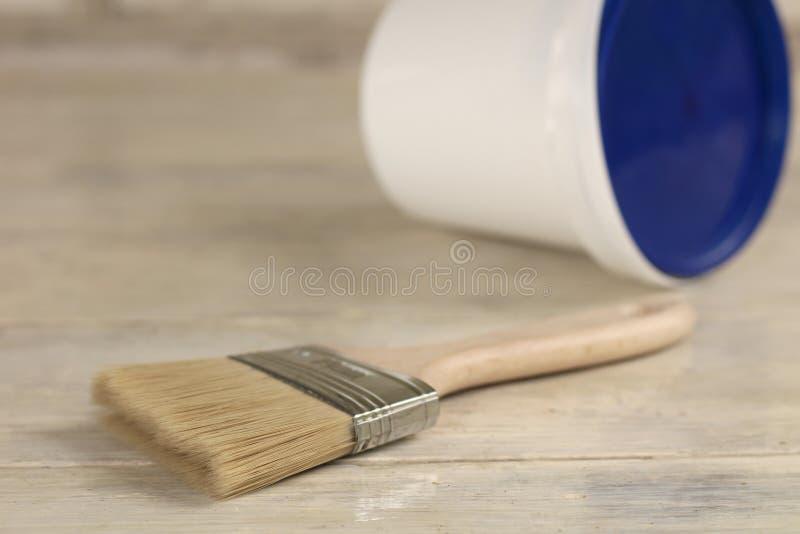 Een verfborstel is naast een plastic verfemmer met een blauw deksel op een oude witte uitstekende houten raad Plaats voor tekst o royalty-vrije stock afbeeldingen