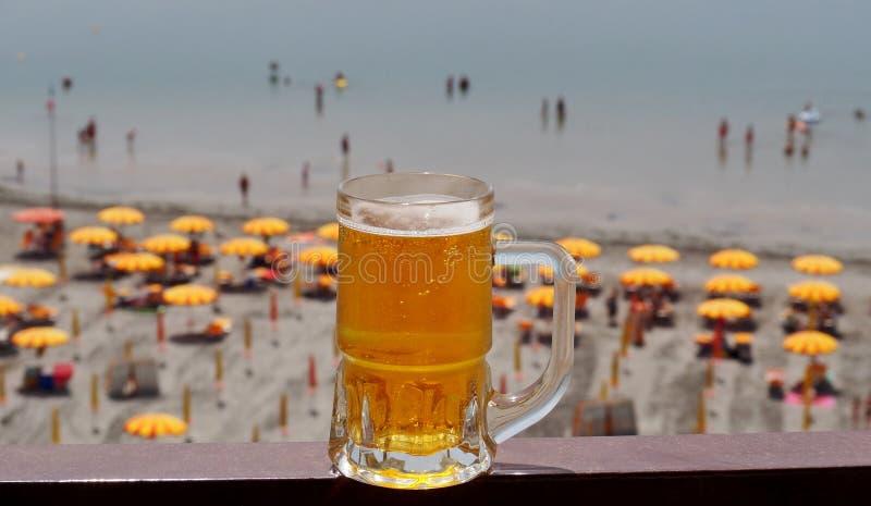 Een verfrissend glas bier over een strandtoevlucht met parasols en mensen het baden royalty-vrije stock afbeeldingen