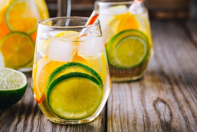 Een verfrissende de zomer ijskoude drank Witte wijnsangria in glas met kalk, citroen en sinaasappel stock foto