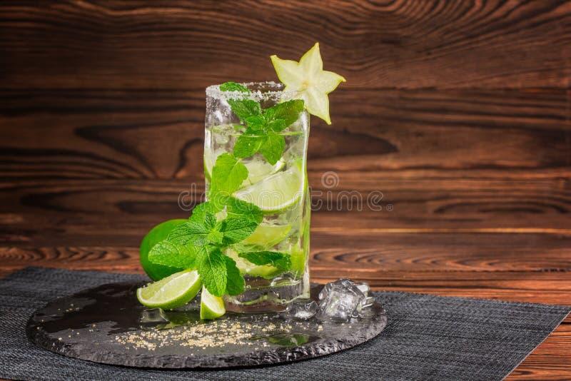 Een verfrissende mojitococktail op een houten achtergrond Kalkmojito met rum, munt en carambola Glas van alcoholdrank De ruimte v stock fotografie