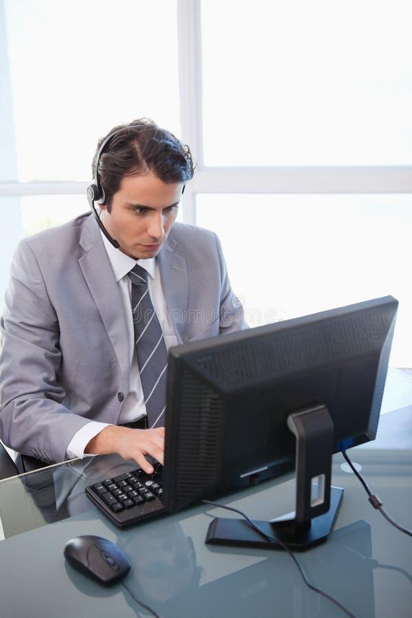 Een verkoopmedewerker die met een monitor werkt stock foto