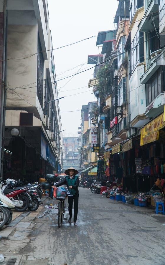 Een verkoper met haar fiets op Dong Xuan Market stock foto's