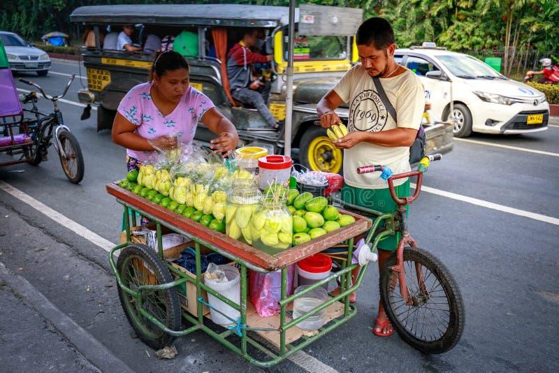 Een verkoper van het straatvoedsel snijdt verse groene mango die op foo verkoopt stock foto