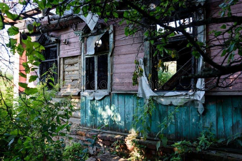 Een verlaten blokhuis met een wilde tuin stock foto's