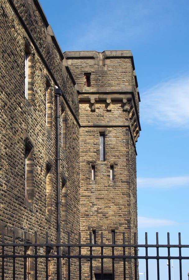 Een verlaten victorian Brits steen institutioneel gebouw dat door een omheining typisch van 19de militaire eeuw en gevangenis wor royalty-vrije stock afbeelding