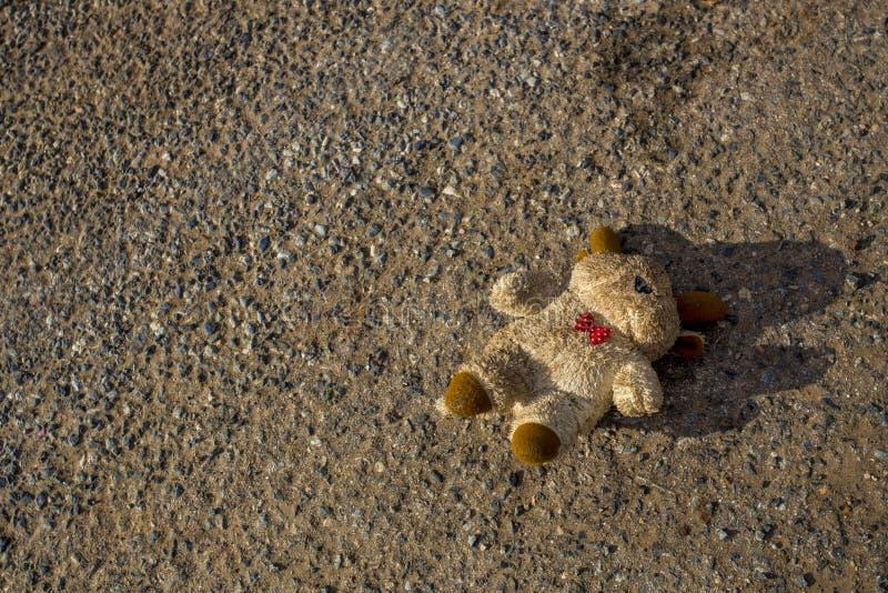 Een verloren daling van de beerpop neer en verloren op de straat De beer is vuil en verloor het oog stock foto