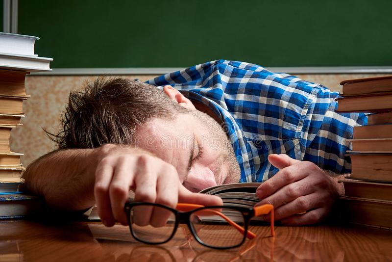 Een vermoeide en gemartelde slordige student met glazen slaapt bij een lijst met stapels boeken stock foto