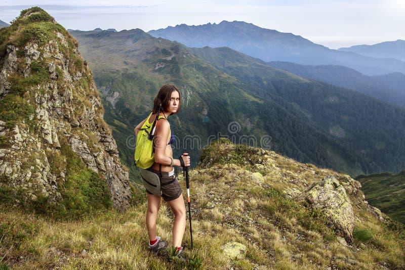 Een vermoeide, gemartelde vrouw - een toerist met een het lopen rugzak bekijkt met haat de fotograaf die haar op moeilijk leidde stock fotografie