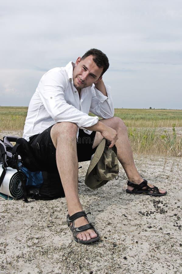 Een vermoeide reiziger zit op zijn rugzak stock fotografie