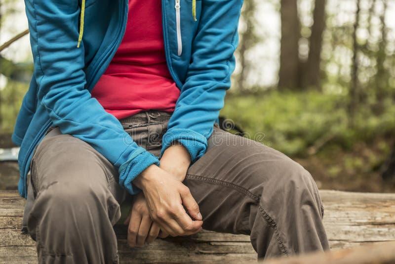 Een vermoeide toerist rust zitting op een logboek, in het bos, op een vage achtergrond van bomen en een meer royalty-vrije stock foto
