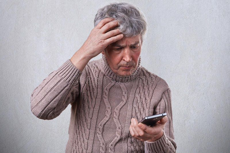 Een verontruste rijpe mens die zijn hand op zijn grijs hoofd houden terwijl het gebruiken van smartphone die sommige nieuws in In stock foto