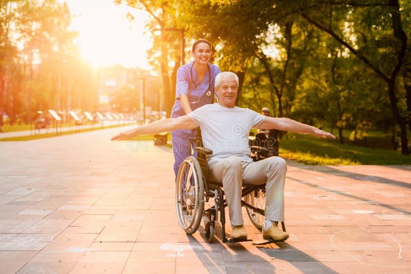 Een verpleegster bevindt zich achter een oude mens, die in een rolstoel zit en zijn wapens zoals vleugels plaatste stock foto's