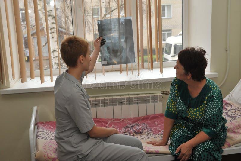 Een verpleegster en een bejaarde patiënt letten op een Röntgenstraal in het ziekenhuis royalty-vrije stock afbeeldingen