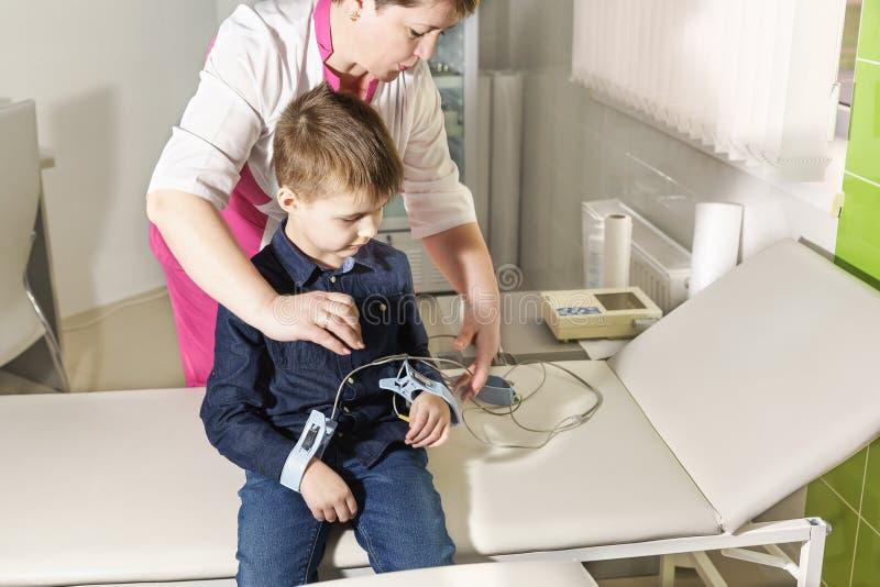 Een verpleegster maakt elektroden aan de jongen vast om het cardiogram te verwijderen stock fotografie