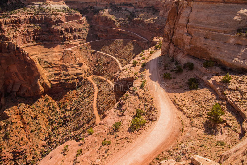 Een verraderlijke weg daalt in een woestijncanion stock fotografie