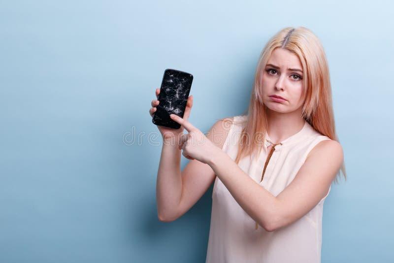 Een verrast meisje toont op het gebroken scherm van de telefoon in haar hand en kijkt recht tegen een blauwe achtergrond stock afbeeldingen