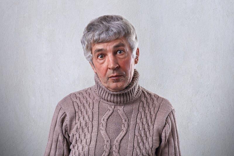 Een verraste oude mens met donkere ogen die rimpels op zijn gezicht en grijs haar hebben die bruine sweater dragen die direct in  royalty-vrije stock foto