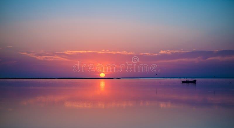 Een verre boot in het stille overzees op schilderachtige zonsondergangachtergrond royalty-vrije stock foto's