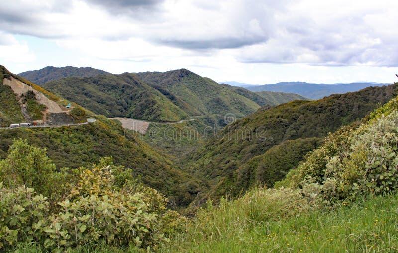 Een verre vallei in Nieuw Zeeland De vrachtwagens zijn op de weg en de bouwvoertuigen werken stock afbeelding