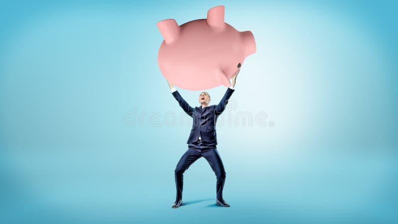 Een verrukte zakenman steunt een reus ten val gebracht spaarvarken over zijn hoofd stock afbeelding