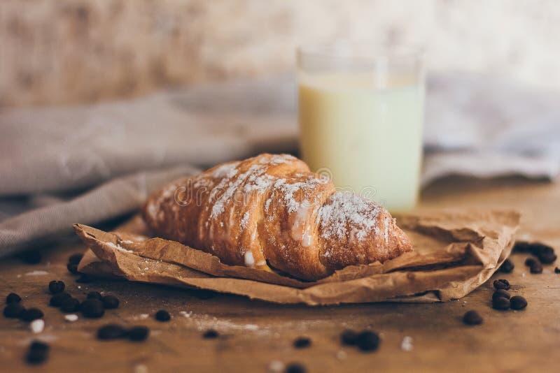 Een vers heerlijk die croissant met suikerpoeder op het ambachtdocument op de houten lijst dichtbij het glas witte melk wordt beh stock afbeelding
