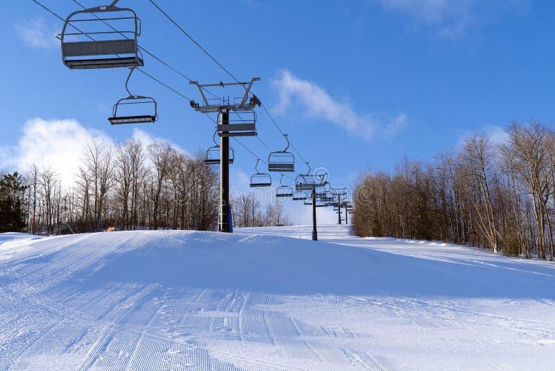Een vers verzorgde looppas met een stoeltjeslift bij een skiheuvel stock foto's