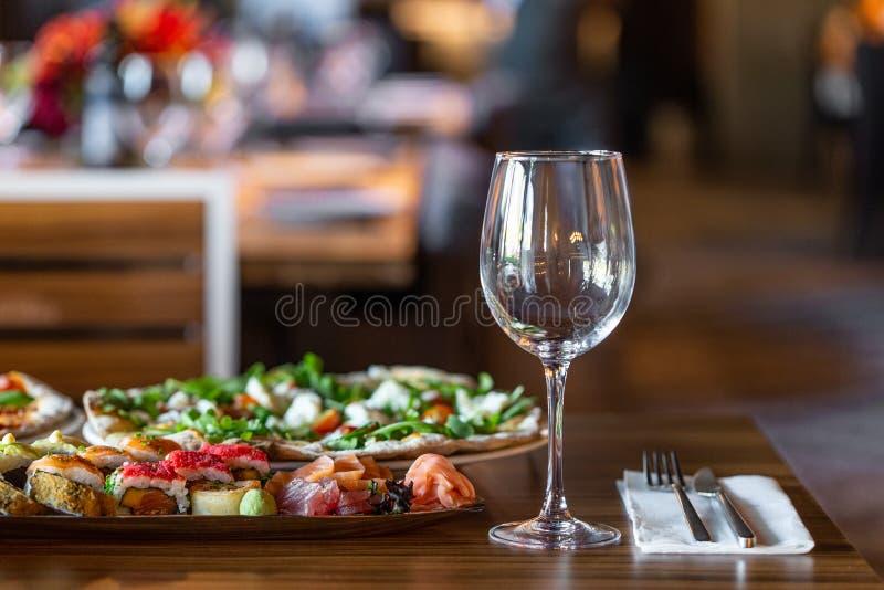 Een verscheidenheid van die voedsel op de lijst in een restaurant van pizza, sushi wordt gemaakt Op een vage achtergrond van het  stock foto's