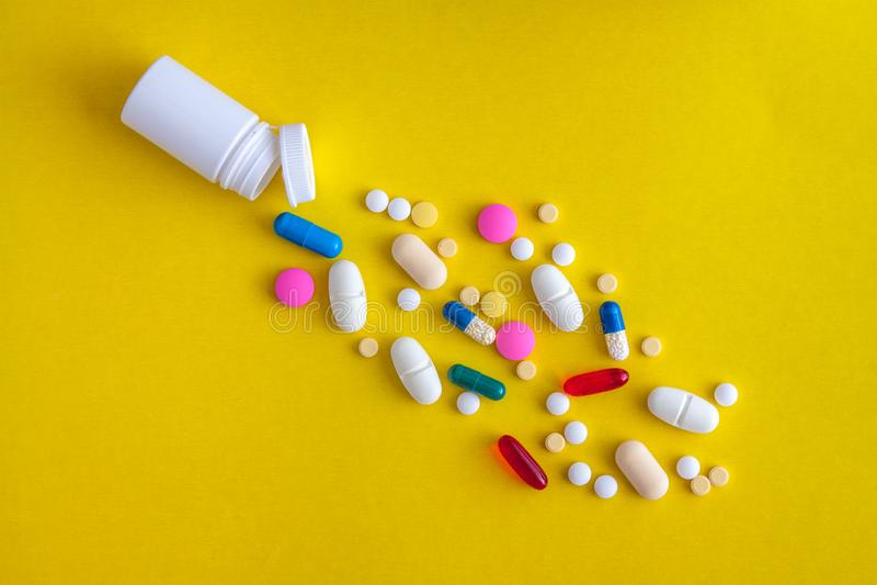 Een verscheidenheid van geneeskrachtige pillen en pillen goten uit het flesje op een gele achtergrond Vlak leg De ruimte van het  royalty-vrije stock afbeelding