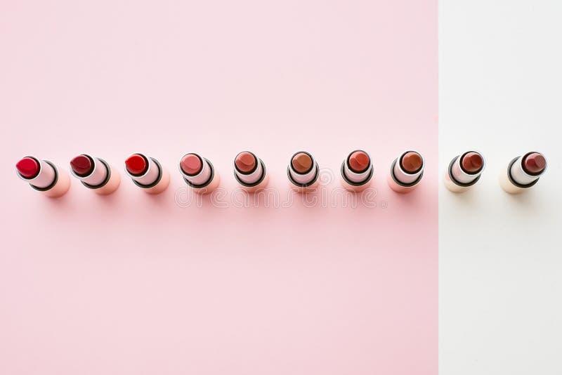 Een verscheidenheid van lippenstiften worden opgesteld op pastelkleur roze en beige achtergronden De lippenstiften worden opgeste stock afbeelding