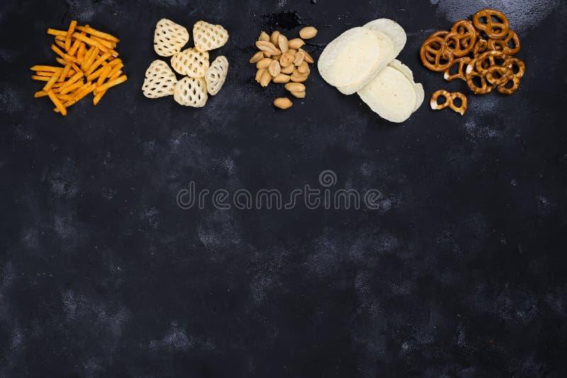 Een verscheidenheid van snacks en snacks voor bier op een concrete zwarte lijst stock foto