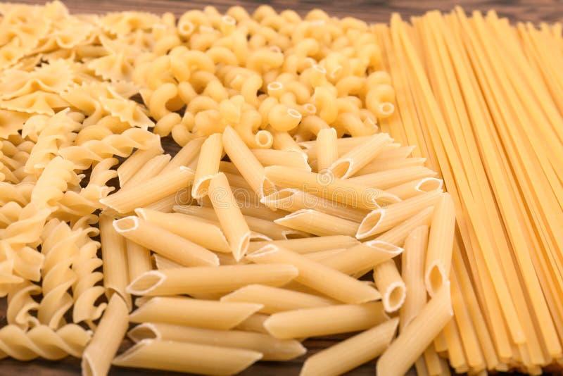 Een verscheidenheid van types en vormen van Italiaanse droge deegwaren op een houten achtergrond Ongekookte, harde, ruwe en droge stock fotografie