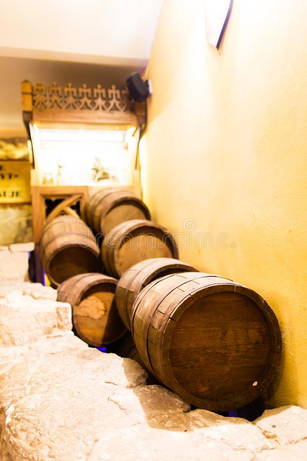 Een verscheidenheid van verschillende houten vaten liggen op de baksteenvloer dichtbij de muur van winehouse royalty-vrije stock afbeeldingen