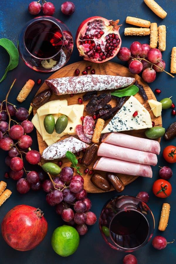 Een verscheidenheid van voorgerecht met rode wijn Diverse worsten en koud vlees, kaas met vorm, fruit De hoogste vlakke mening, l royalty-vrije stock fotografie