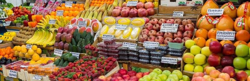 Een verscheidenheid van vruchten en bessen op de teller op de markt stock afbeeldingen