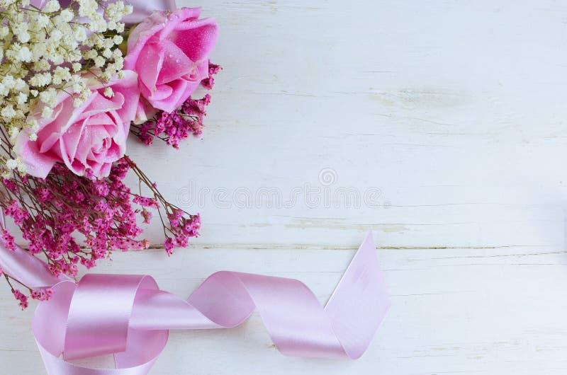 Een verse bloemenregeling van zachte roze rozen en droge bloemen met mooi satijnlint op rustieke witte gewassen houten lijst stock afbeeldingen