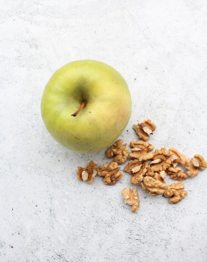 Een verse groene appel en okkernoten stock afbeeldingen