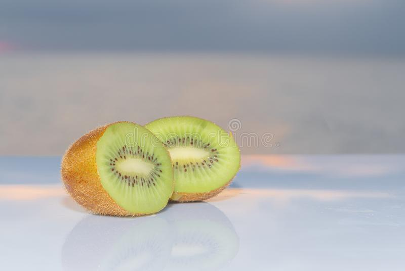 Een verse groene kiwibesnoeiing in half geïsoleerd op een blauwe achtergrond - Harige groene kiwi - plaatst uit elkaar om tekst t royalty-vrije stock afbeelding