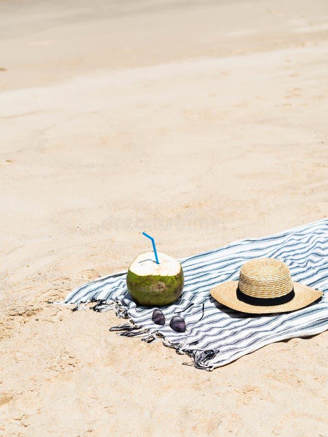 Een verse jonge kokosnoot is klaar te eten en een het strohoed van vrouwen op een handdoek op een zandig strand Het tropische con stock afbeeldingen