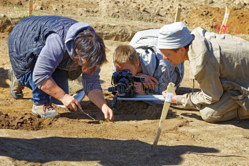 Een verslaggever en een cameraman die een rapport over archeologische uitgravingen filmen stock foto's