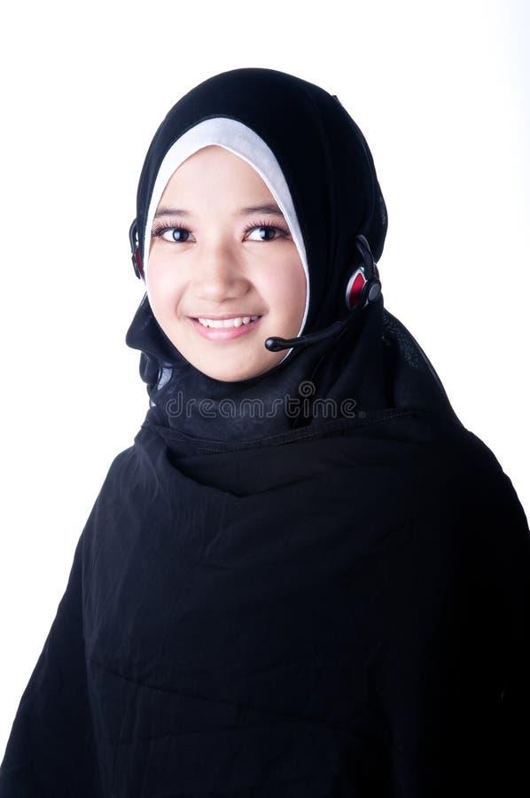 Een versluierde vrouw glimlacht gebruikend communicatiemiddelen stock afbeeldingen