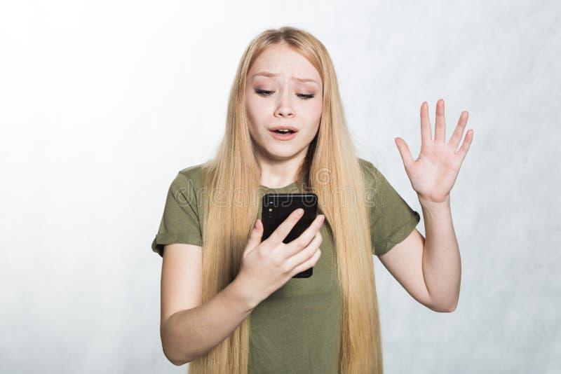 Een in verwarring gebrachte en ongerust gemaakte jonge vrouw die een smartphone houden, die met een verraste uitdrukking kijken stock afbeeldingen