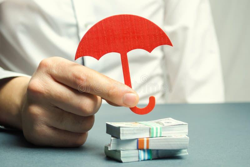 Een verzekeringsagent houdt een rode paraplu over dollarrekeningen Besparingenbescherming Het houden van geldbrandkast Investerin royalty-vrije stock afbeeldingen